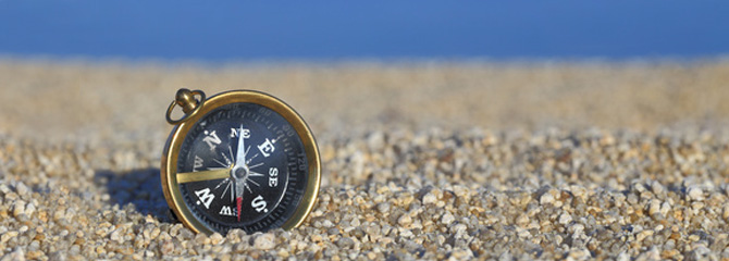 Old compass on the beach with sand and sea